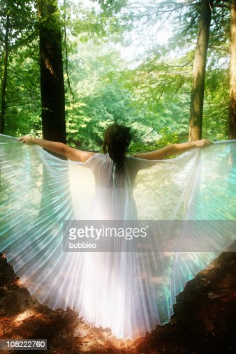 Young Woman Spreading White Wings in Forest