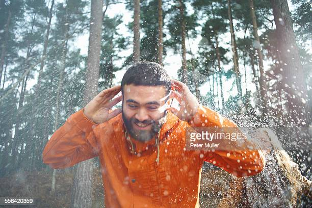 Young woman sprinkling boyfriend with water in forest