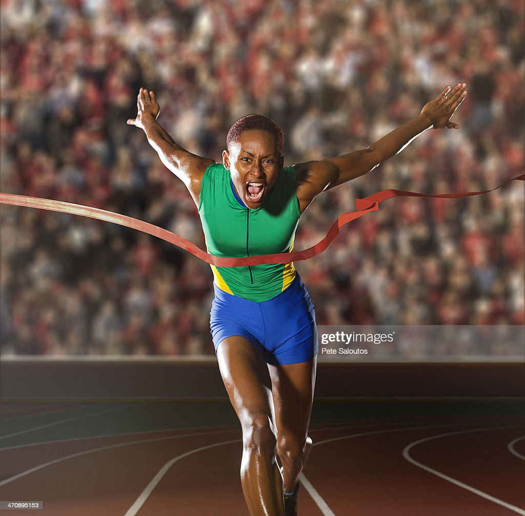 Young woman sprinting through winners tape in stadium : Stock Photo