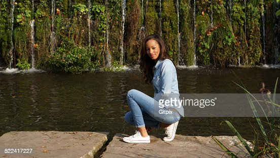 young woman squatting on a stone stock foto getty images. Black Bedroom Furniture Sets. Home Design Ideas