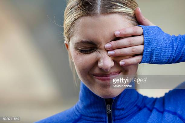 Young woman squinting at discomfort in eye
