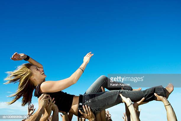 Young woman stage diving, view against clear blue sky