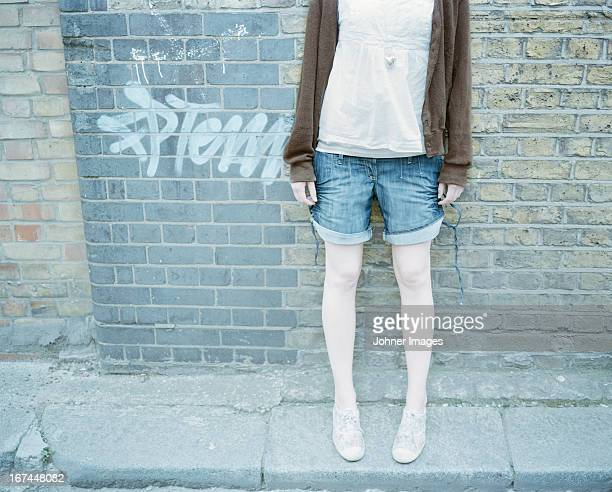Young woman standing against brick wall, low section
