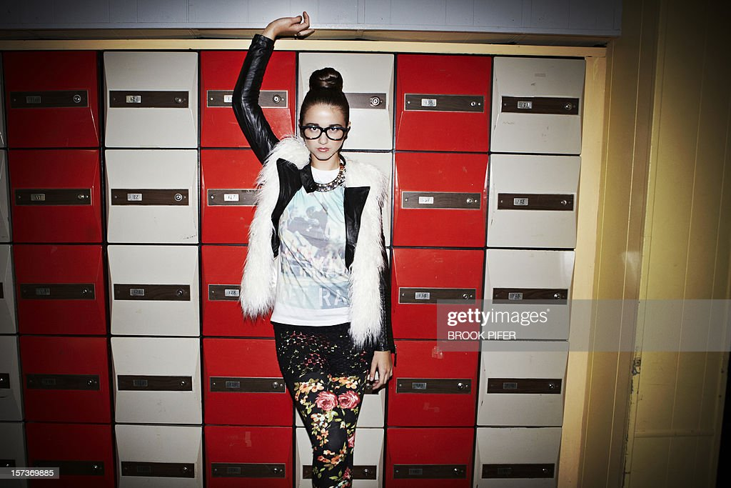 Young woman standing against lockers