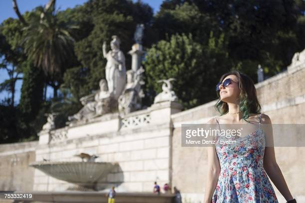 Young Woman Standing Against Sculptures On Sunny Day