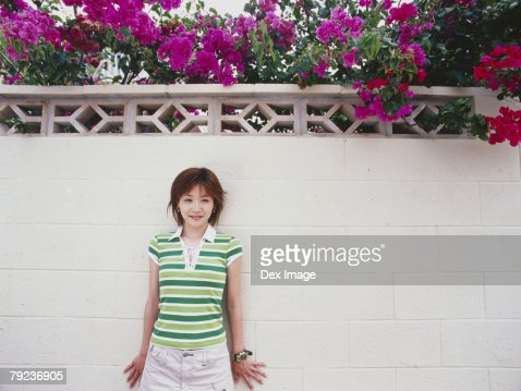 Young woman standing against wall : Stock Photo
