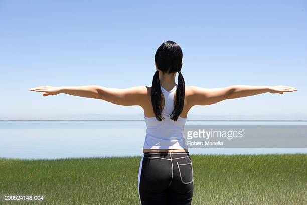 Young woman standing arms extended in field, rear view
