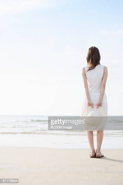 Young woman standing at beach, rear view