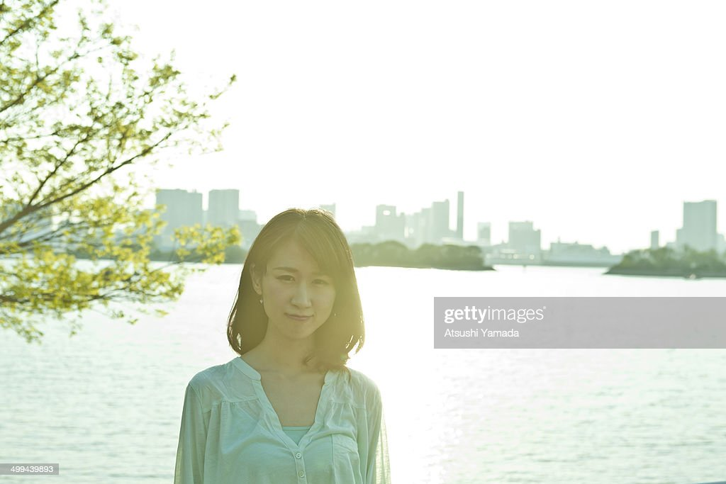 Young woman standing at riverside,smiling