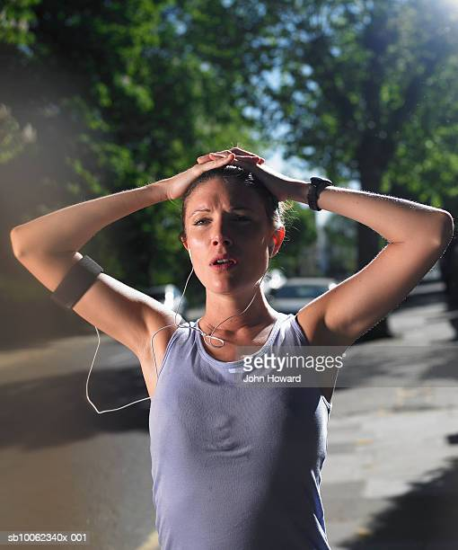 Young woman standing at street with raised arms, resting after jogging