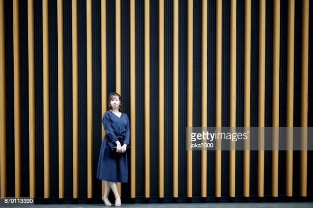 壁の前に立っている若い女性