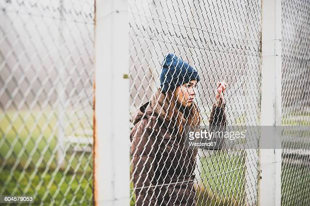 Young woman standing behind mesh wire fence