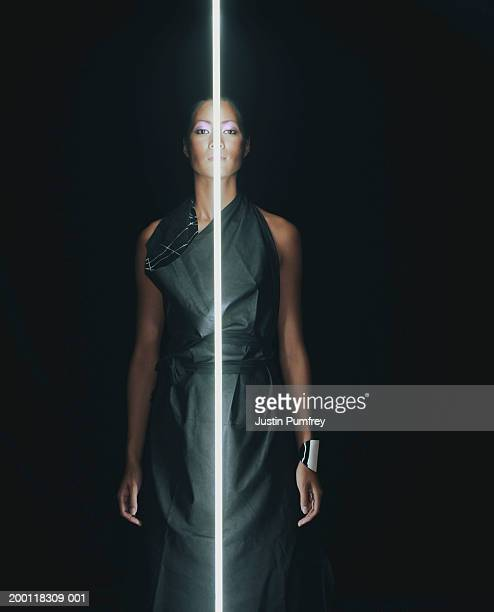 Young woman standing behind vertical beam of light, portrait