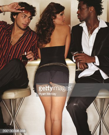 Young woman standing between two men at bar : Foto de stock