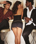 Young woman standing between two men at bar