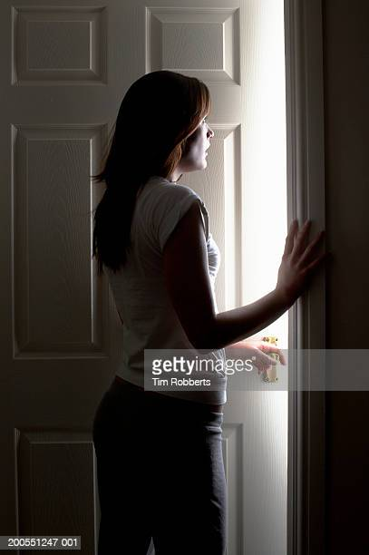 Young woman standing by doorway