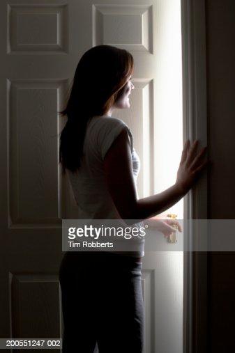 Young woman standing by doorway, smiling : Foto de stock
