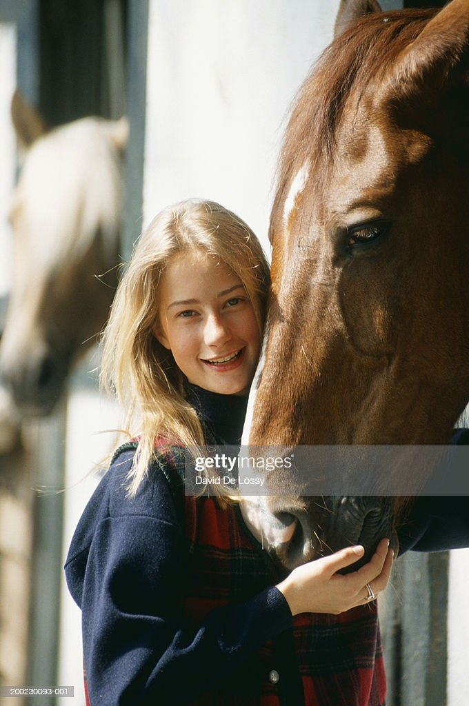Young woman standing by horse in stable, outdoors, portrait : Stock Photo