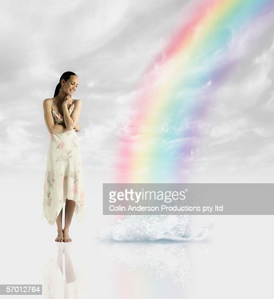 Young woman standing by rainbow's end : Foto stock