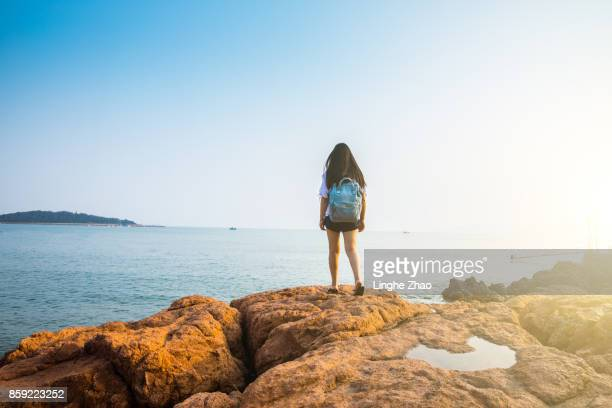 Young woman standing by sea