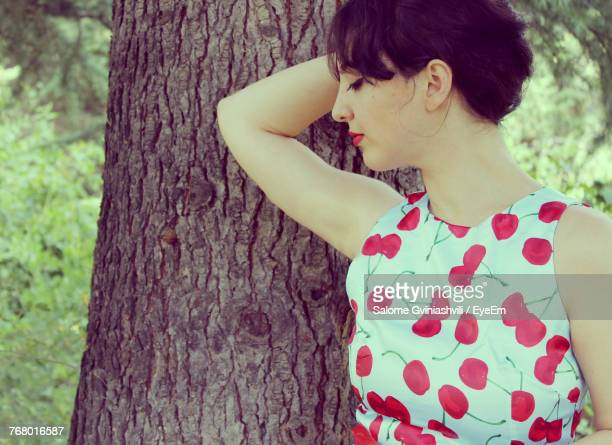Young Woman Standing By Tree Trunk