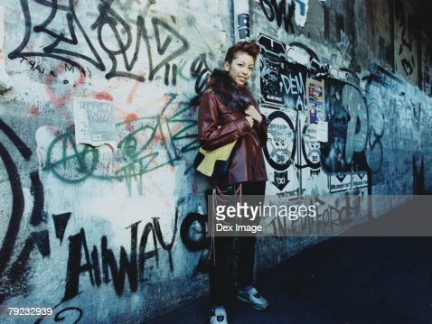 Young woman standing by vandalized wall : Stock Photo