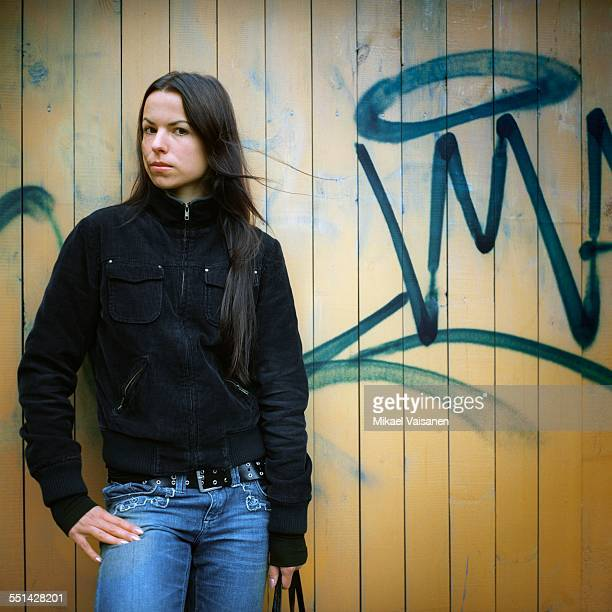 Young Woman Standing by Wall