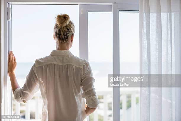 Young woman standing by window at home