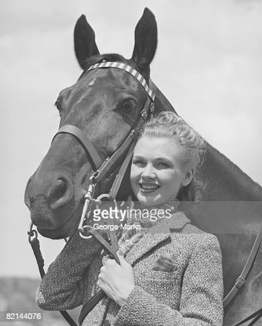 Young woman standing close to horse, (B&W), portrait : Stock Photo