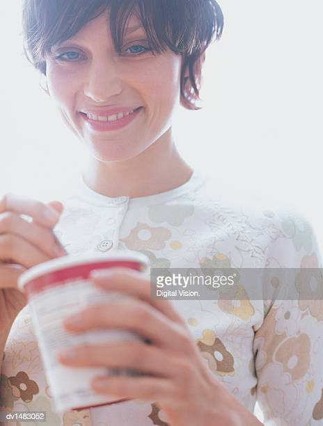 Young Woman Standing Holding an Ice Cream Container