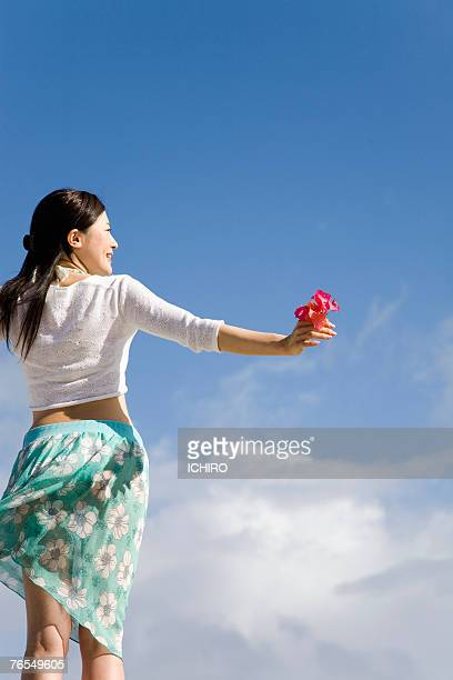 Young woman standing, holding flowers, outdoors, low angle, rear view