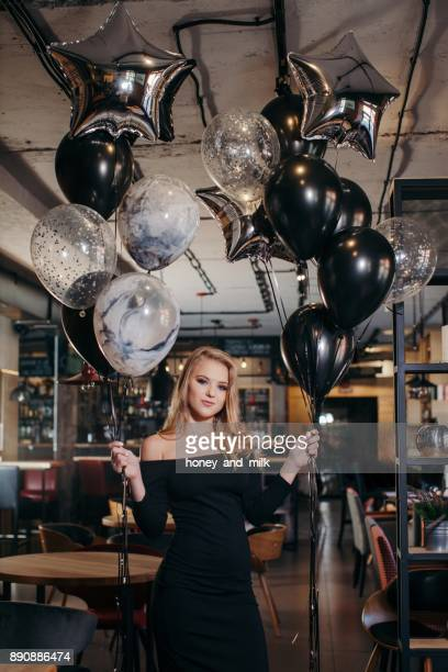 Young woman standing in a bar holding balloons