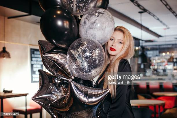 Young woman standing in a cafe holding balloons