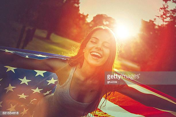 Young woman standing in a meadow holding american flag