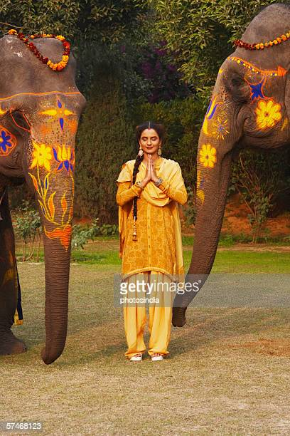 Young woman standing in a prayer position with two decorated elephants