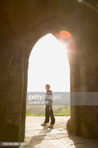 Young woman standing in archway of St. Michael's Tower, portrait : Stock Photo