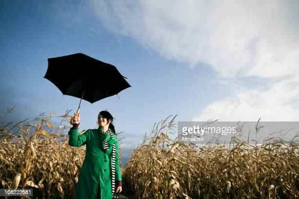 Young Woman Standing in Corn Field Holding Umbrella