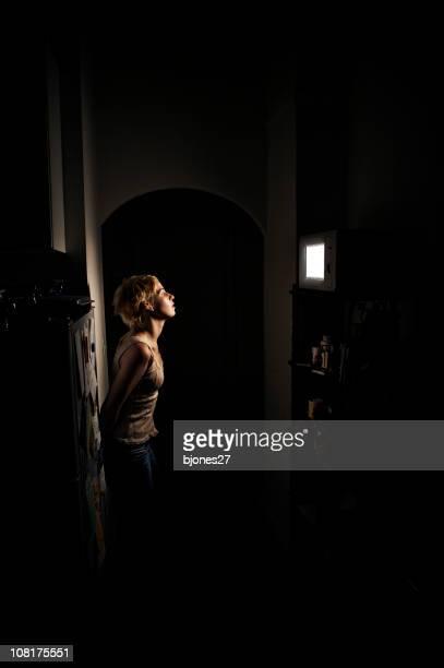 Giovane donna in piedi in Dark aspetta un microonde per finitura