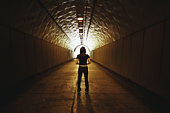 Young woman standing in dimly lit tunnel, rear view