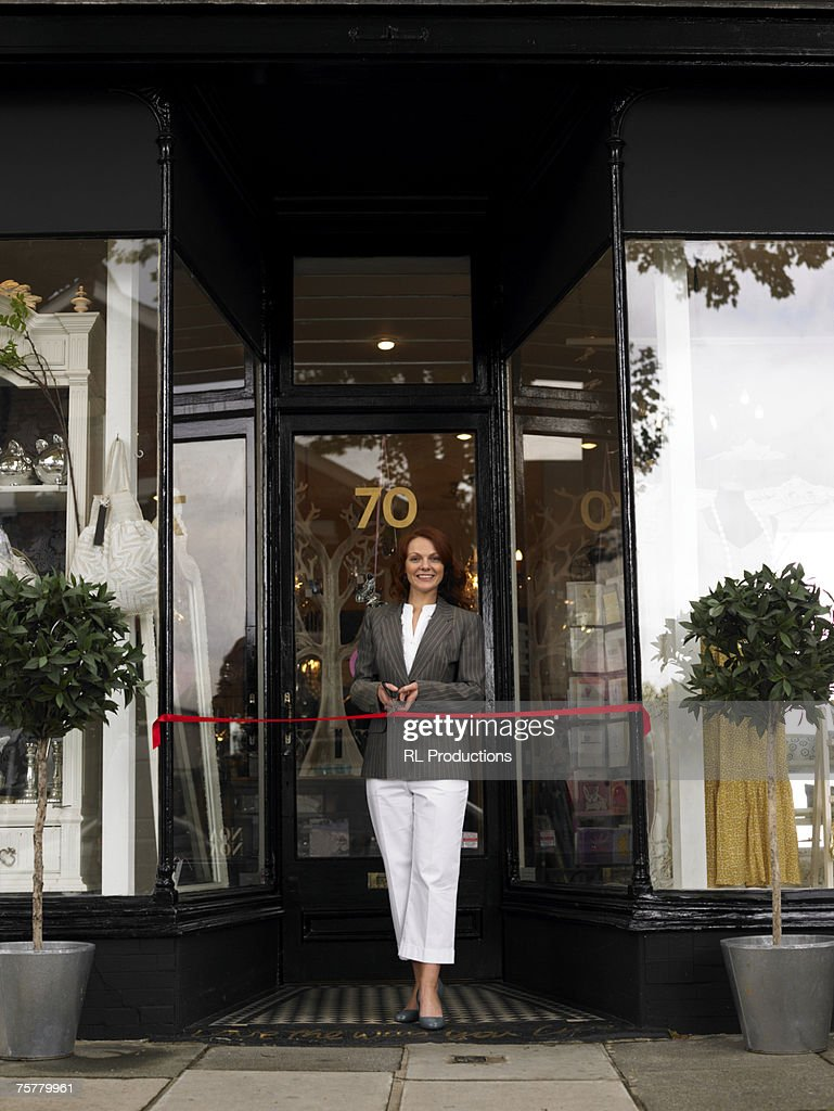 Young woman standing in entrance of new shop behind red ribbon, smiling, portrait