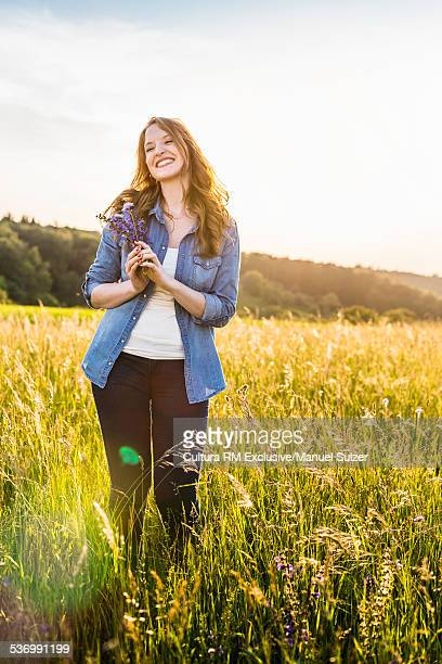 Young woman standing in field holding wild flowers