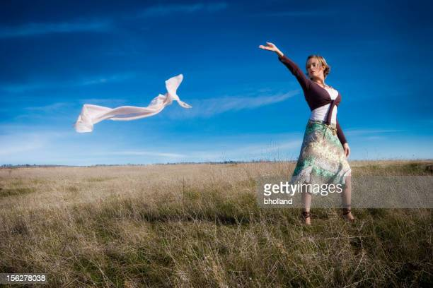 Jeune femme debout dans le champ Lettting vent Prenez écharpe