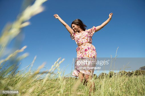 Young woman standing in field with arms raised : Bildbanksbilder