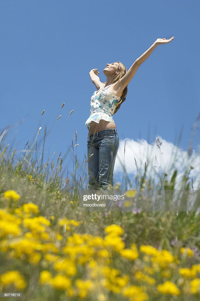 Young woman standing in field with open arms low angle view side view : Stock Photo