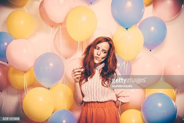 Jovem de pé em frente a uma parede do balão