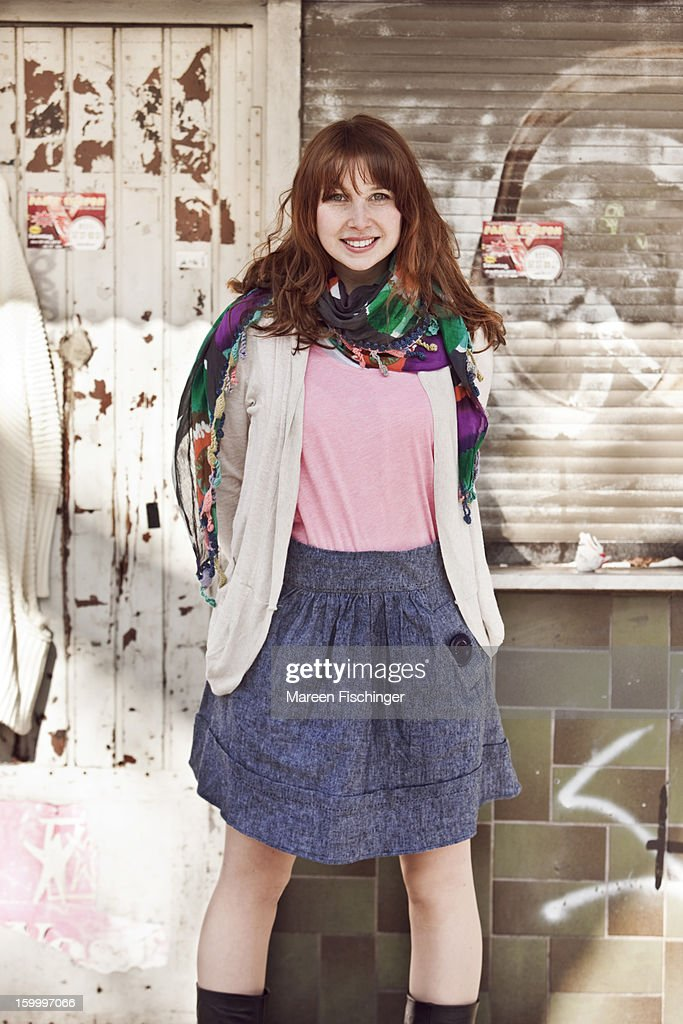 Young woman standing in front of an urban backdrop : Stock Photo
