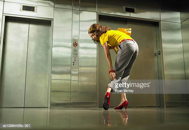 Young woman standing in front of elevators inspecting trousers and shoe, rear view