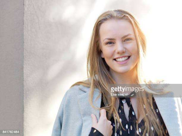 young woman standing in front of light filled concrete wall smiling
