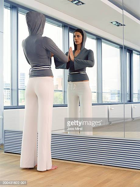 Young woman standing in front of mirror meditating