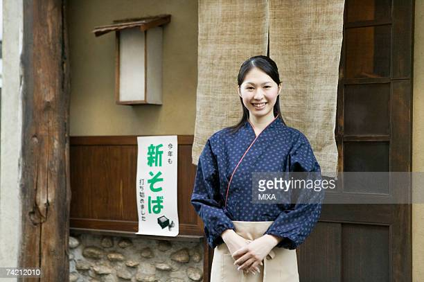 Young woman standing in front of restaurant
